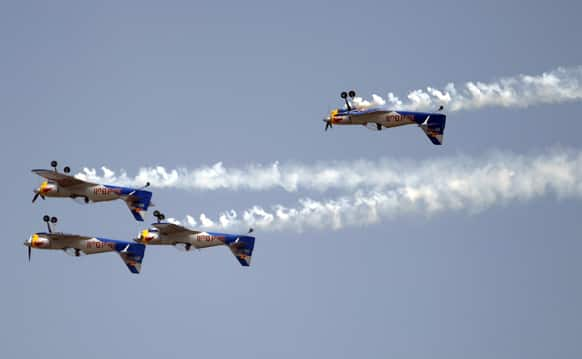 Flying Bulls Zlin 50LX single-engine and single-seater aerobatic display team from the Czech Republic perform inverted flight on the fourth day of the Aero India 2013 at Yelahanka air base in Bangalore.