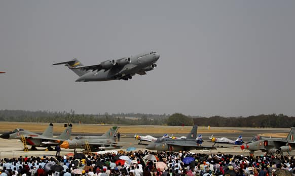 Visitors watch U.S. Air Force C-17 Globemaster III, a cargo plane, fly over other aircraft on the fourth day of the Aero India 2013 at Yelahanka air base in Bangalore.
