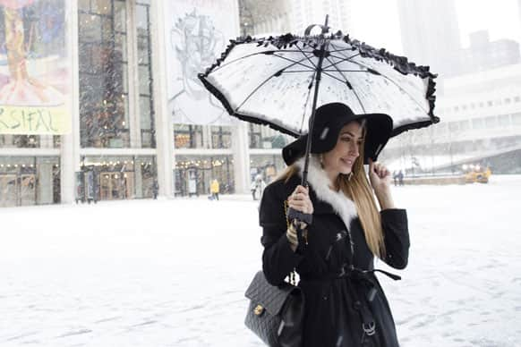 Lauren Rae Levy, of Manhattan, stands outside the Metropolitan Opera House in the snow at Lincoln Center during Fashion Week.
