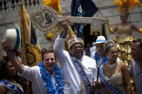The mythical jester figure who reigns over Carnival, this year`s King Momo; the crowned and costumed Milton Rodrigues Junior, center, holds up the key of the city that was given by Rio de Janeiro`s Mayor Eduardo Paes, left, at the official ceremony kicking off the five-day bash, in Rio de Janeiro, Brazil.