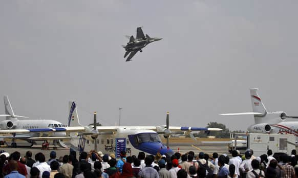 Visitors watch a Sukhoi Su-30 fighter aircraft fly over other aircraft on display on the third day of the Aero India 2013 at Yelahanka air base in Bangalore.