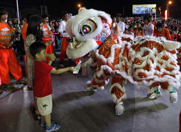 Myanmar Chinese boy offer paper money to a traditional Lion dancer during an event marking incoming Lunar New Year, at a shopping mall in Yangon, Myanmar.