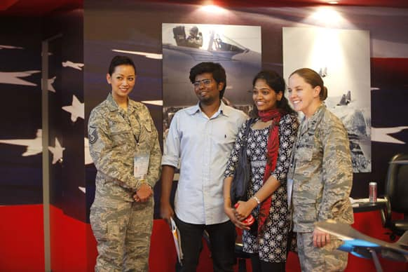Visitors pose with US Air Force officials at their booth on the second day of the Aero India 2013 at Yelahanka air base in Bangalore.