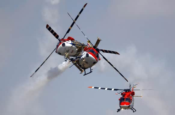 Indian Air Force helicopters cross paths while performing an aerobatic flight on the opening of the Aero India 2013 at Yelahanka air base in Bangalore.
