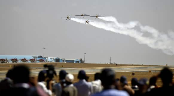 Journalists watch the Flying Bulls Zlin 50LX single-engine and single-seater aerobatic display team from the Czech Republic perform on the opening of the Aero India 2013 at Yelahanka air base in Bangalore.