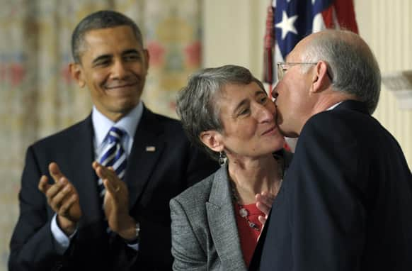 President Barack Obama watches as his Interior Secretary nominee, REI Chief Executive Officer Sally Jewell, center, gets a kiss from outgoing Interior Secretary Ken Salazar, in the State Dining Room of the White House in Washington, where the president announced that Jewell is his choice to replace Salazar.