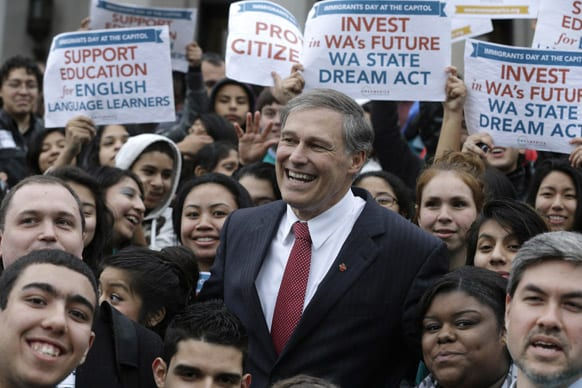 Washington Gov. Jay Inslee, center, poses for a group photo with with participants at a rally organized by the group OneAmerica supporting immigration rights, education, and other issues, at at the Capitol in Olympia, Wash.