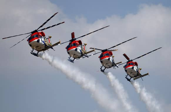 Indian Air Force helicopters perform aerobatic flight on the opening of the Aero India 2013 at Yelahanka air base in Bangalore.