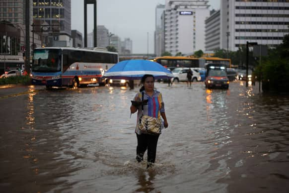 A woman walks on a flooded street following a heavy rain at the main business district in Jakarta, Indonesia.