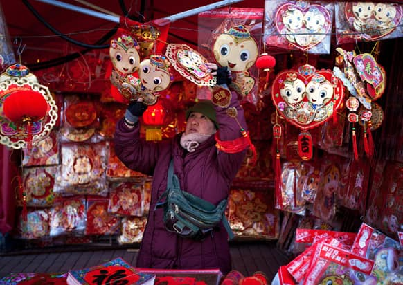 A vendor arranges decorations for Chinese New Year on display for sale at her store in Beijing. Chinese will celebrate the Lunar New Year on Feb. 10 this year which marks the Year of Snake.