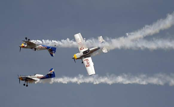 Red Bull`s Zlin 50LX single-engine single-seater aircrafts perform aerobatic flight during rehearsals on the eve of the Aero India 2013 at Yelahanka air base in Bangalore.