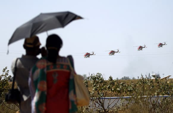 A couple watches Indian Air Force helicopters perform formation flight during rehearsals ahead of the Aero India 2013 in Yelahanka air base in Bangalore.