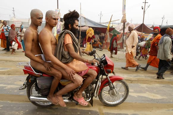 Two Hindu holy men of the Juna Akhara are being taken on a motorcycle by their teacher at Sangam during the Maha Kumbh festival in Allahabad.