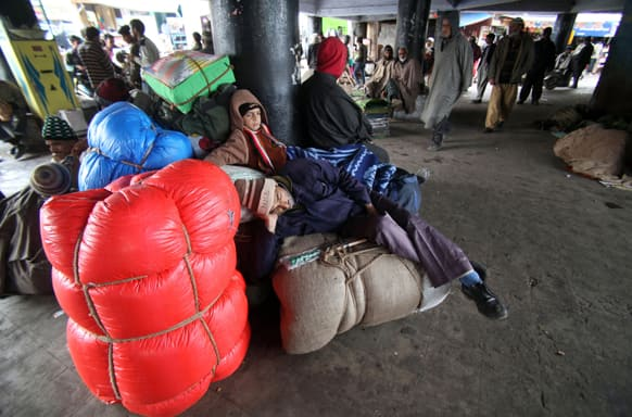 Stranded passengers rest on luggage as they wait for the Jammu-Srinagar highway to reopen at a bus station in Jammu.
