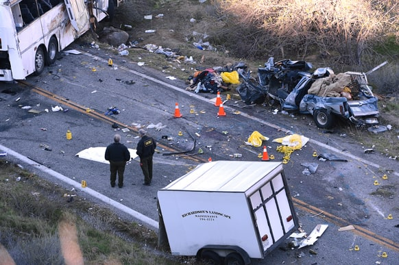 Authorities work at the scene of Sunday`s fatal tour bus crash on Highway 38 north of Yucaipa, Calif., that left at least eight people dead and dozens injured. The cause of the Sunday crash east of Los Angeles remained under investigation.