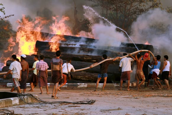 People try to extinguish a blaze on a pile of teak logs those caught fire from a burning oil ship that sank in Hlaing river, in Yangon, Myanmar.