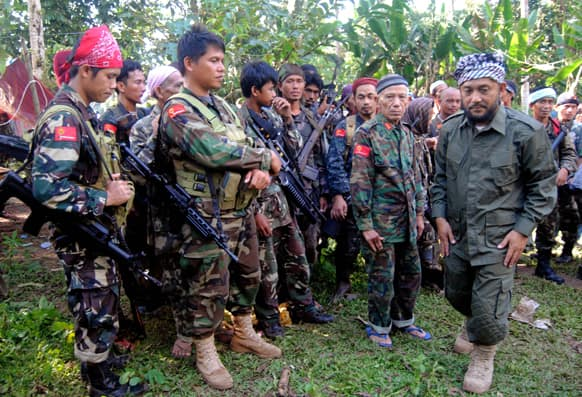 Rebel commander Khabir Malik, right, of the Moro National Liberation Front, which has an autonomy deal with the government, talks to his comrades at their camp in the volatile island of Jolo, Sulu province in southern Philippines.
