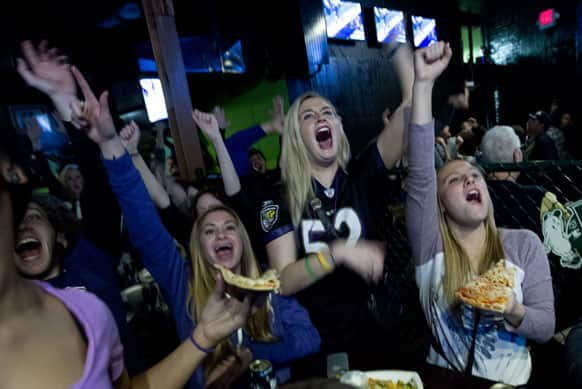 Baltimore Ravens fans celebrates after their team scored the first touchdown against San Francisco 49ers, at local pub in Baltimore.