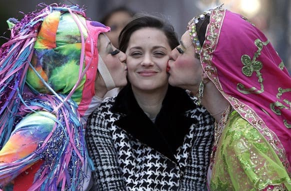 Actress Marion Cotillard, of France, center, the Hasty Pudding Woman of the Year, is kissed by Harvard University theatrical students Renee Rober, left, and Ben Moss, right, as they ride in the back of a convertible during a parade through Harvard Square, in Cambridge, Mass.