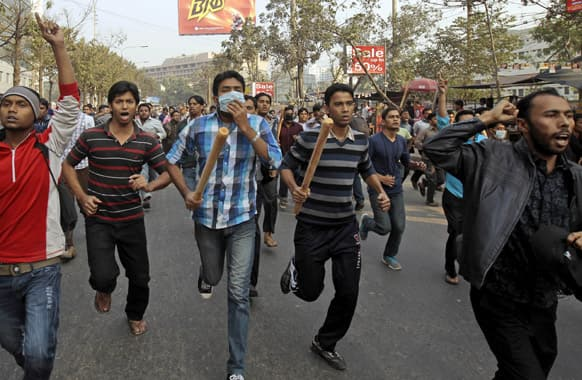 Jamaat-e-Islami activists armed with sticks march on a street in Dhaka. Hundreds of supporters of Bangladesh`s main Islamist party attacked police Monday in a busy commercial district in the nation`s capital, injuring many including at least eight security officers, an official said.