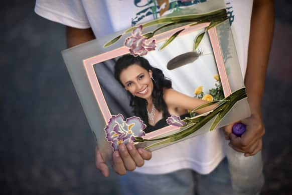 A youth holds a photograph of his sister Pamella Lopes, who died in a nightclub fire, in a public square near the club in Santa Maria, Brazil.