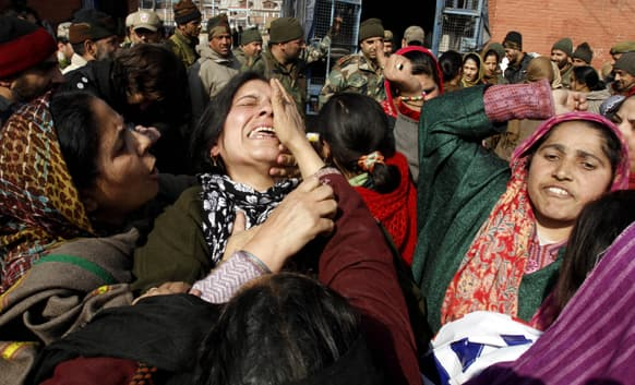 A worker of anganwadi, or government sponsored child and mother care, cries as others shout slogans during a protest in Srinagar.