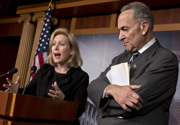 Sen. Kirsten Gillibrand, D-N.Y., left, and Sen. Charles Schumer, D-N.Y., right, react after the Senate passed a $50.5 billion emergency relief measure for Superstorm Sandy victims at the Capitol in Washington.