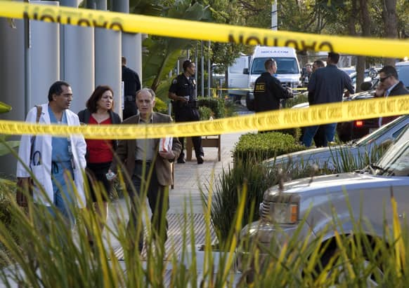 Police investigate as medical personnel exit the scene outside a medical office near Hoag Hospital where shots were fired in Newport Beach, Calif. Police say a doctor has been shot and killed and a man is in police custody.