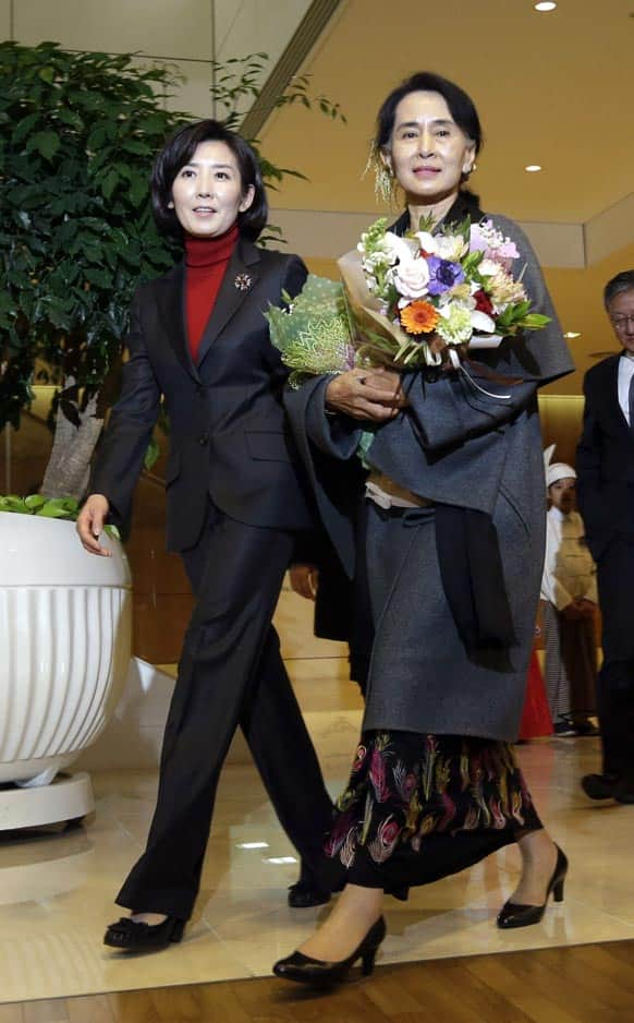 Myanmar opposition leader Aung San Suu Kyi, right, is escorted by the 2013 Pyeongchang Special Olympics Organizing Committee chairperson Na Kyung-won upon her arrival at Incheon International Airport in Incheon, west of Seoul, South Korea.