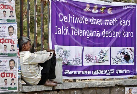 A man sits near a banner during a protest at the Indira Park in Hyderabad.