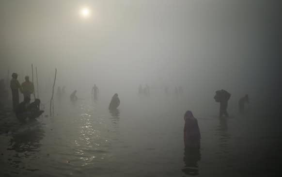 Hindu pilgrims take a dip at Sangam, the confluence of the Ganges, Yamuna and the mythical Saraswati River, during the Maha Kumbh festival in Allahabad.