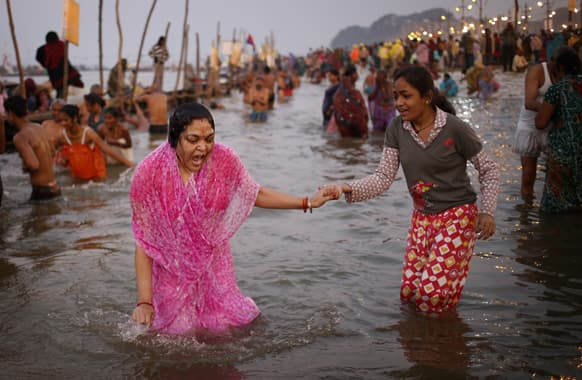 A Hindu devotee gasps after a dip in the cold water at