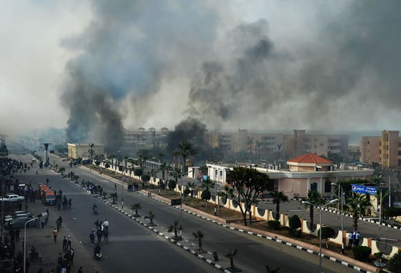 Smoke rises after Egyptian protesters clash with police, unseen, in Port Said, Egypt.
