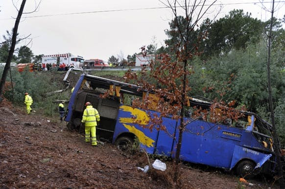 Portuguese firefighters work around the wreckage of a bus which ran off the road and crashed into a ravine, killing 10 people and injuring 33, officials said, in Serta.
