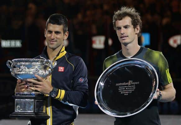 Serbia`s Novak Djokovic, left,holds his trophy after defeating Britain`s Andy Murray, right, in the men`s final at the Australian Open tennis championship in Melbourne.