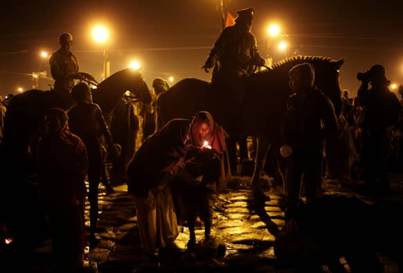 Policemen patrol an area as hindu devotees light a lamp to perform rituals at