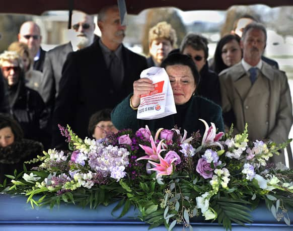 Linda Phiel places a Whopper Jr. sandwich from Burger King on the casket to be buried with her father David Kime, Jr. at Prospect Hill Cemetery in York, Pa.