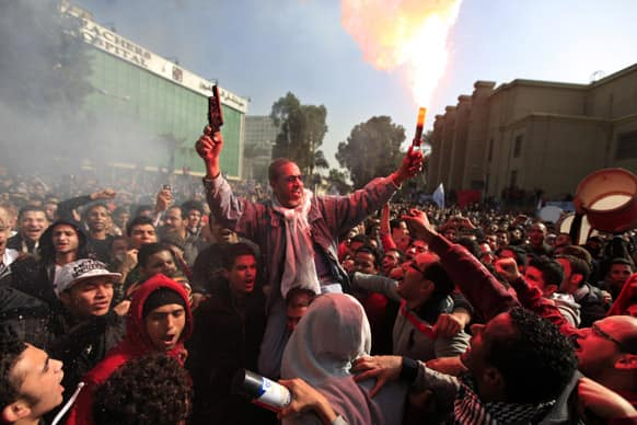 Egyptian soccer fans of Al-Ahly club celebrate a court verdict that returned 21 death penalties in last years soccer violence, inside the club premises in Cairo, Egypt.