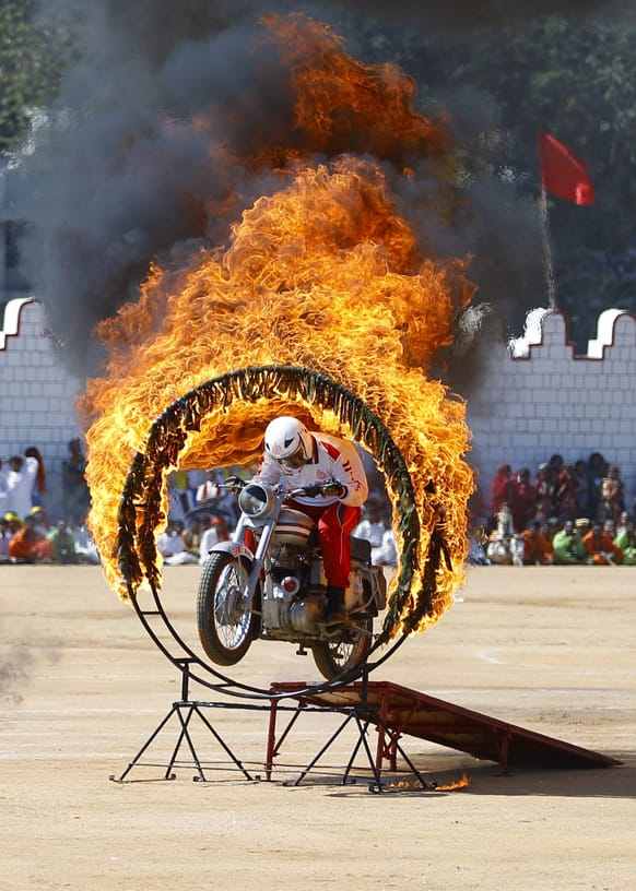 Army soldier performs a stunt by riding through a burning ring during a function to mark India`s Republic Day in Bangalore.