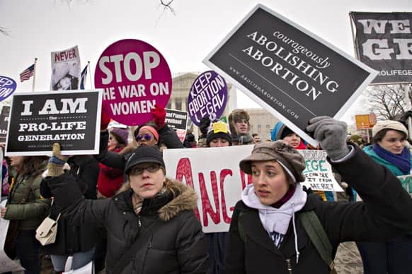 Anti-abortion activists and supporters of legal abortion stand in front of the Supreme Court in Washington.