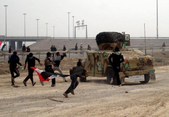 Protesters throw stones towards Iraqi soldiers at a checkpoint during clashes in Fallujah, 40 miles (65 kilometers) west of Baghdad.