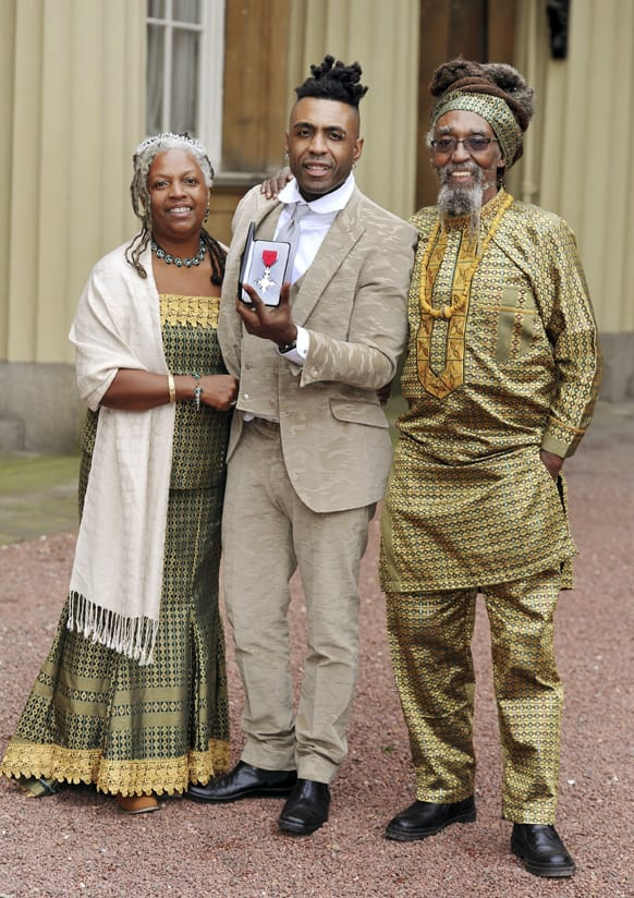 British musician Omar Lye-Fook, centre, with his parents Sonia and Byron, displays his Member of the British Empire (MBE) medal after it was presented to him by the Prince of Wales during the Investiture ceremony at Buckingham Palace in central London.