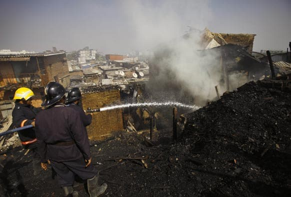 Firefighters spray water as they try to douse a fire in a shanty in Mumbai. A fire has swept through a slum in India`s financial capital Mumbai killing six people and injuring at least seven others.