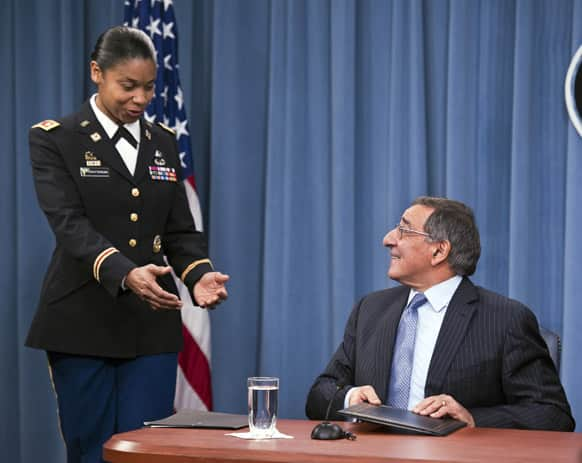 Army Lt. Col. Tamatha Patterson, of Huntingdon, Tenn., waits for Defense Secretary Leon Panetta to hand her the memorandum he has just signed ending the 1994 ban on women serving in combat during a news conference at the Pentagon.