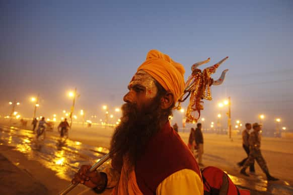 A Hindu holy man carrying a Trident, walks at Sangam, the confluence of rivers Ganges and Yamuna during the Maha Kumbh festival in Allahabad.