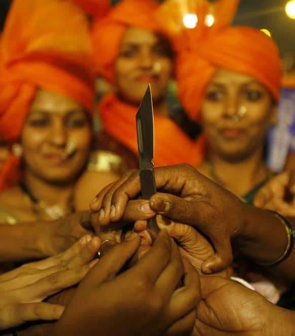 Women reach out their hands to collect knives being distributed by local leaders of Shiv Sena, a right-wing party in Mumbai.