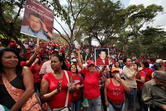 Supporters of Venezuela`s President Hugo Chavez hold photos of him at an event commemorating the 1958 fall of the country`s dictatorship in Caracas, Venezuela.