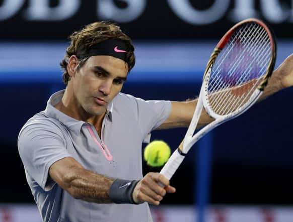 Switzerland`s Roger Federer hits a backhand return to France`s Jo-Wilfried Tsonga during their quarterfinal match at the Australian Open tennis championship in Melbourne.