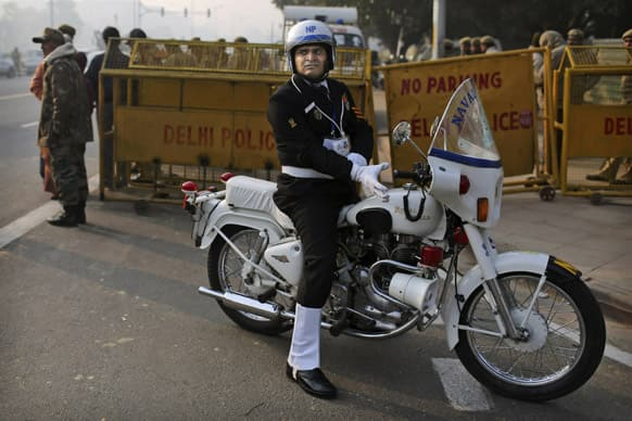 An Indian naval police officer puts on his white gloves as he waits before a dress rehearsal for the annual Republic Day parade in New Delhi.