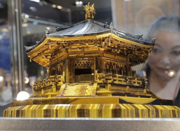 A woman looks at a scale model of a historic Japanese cathedral, the Yumedono or dream hall, of Horyuji temple during the 24th International Jewelry Exhibition in Tokyo.